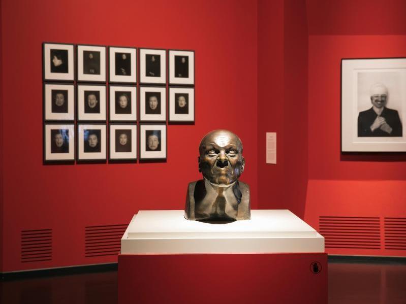 """Deutsches Hygiene-Museum, Ausstellungsraum mit der Plastik """"Charakterkopf Nr. 31: Geruch, der zum Niesen reizt"""", geschaffen von Franz Xaver Messerschmidt um 1775, und """"Schmunzelhilfe"""" 1973, eine Fotografie von Gottfried Helnwein"""